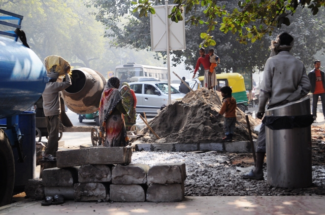 Such scenes of a husband and wife working at a construction site with their children is a common site in India. It is here that the kids start working early as child labour. Photo by C. Rahul in New Delhi.