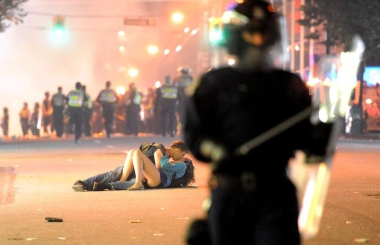While Vancouver city was burning following the riots post their team Canucks' disgraceful defeat in Stanley Cup, a young couple - Scott Jones and his girlfriend Alex Thomas were snapped kissing amidst the commotion.