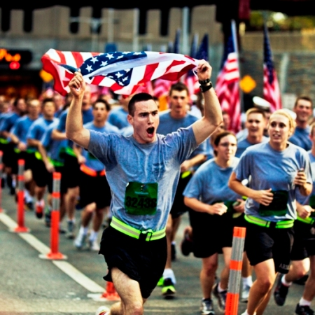 A soldier sprints while carrying an American flag during the New York City Tunnel to Towers Run to raise awareness for military causes in New York. Photo by Randall Clinton.