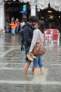 A couple exchange a kiss on a flooded St Mark's square during the first Acqua Alta of the season in Venice. The Acqua Alta is the convergence of high tides and a strong sirocco. Photo by AFP's Andrea Pattaro